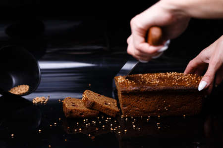 Homemade black bread on a black background. Photo in section.