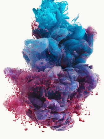 Color drop falling in water creating a Color spread. Isolated on white background. Colorful ink drop. Movement of paint in water. Water coloring.