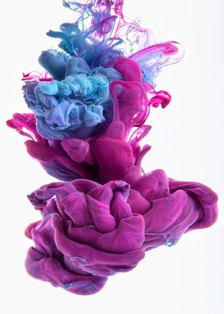 Spadek kolorów w wodzie, sfotografowany w ruchu. Mieszając atramentu w wodzie. Chmura jedwabisty atramentu w wodzie samodzielnie na białym tle. Kolorowy tusz w wodzie kropelek tuszu. Przepływ farby z wodą. Barwienia wody. Zdjęcie Seryjne
