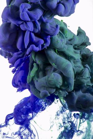 水の下で混合液体の色ドロップの抽象的な芸術的な写真。水の色のカラフルなブレンドです。 白い背景上に分離。