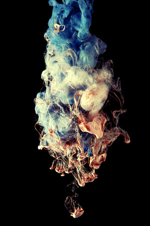 Warm ink drops of color spread and mix under water. Colorful abstract smoke cloud, Isolated on black color background.
