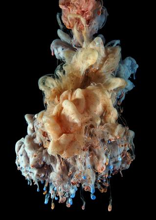 カラーの見開きのインク滴を温めるし、水の下でミックスします。カラフルな抽象的な煙雲、黒一色の背景に分離されました。 写真素材
