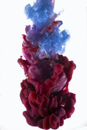 Vloeibare kleur daling van dynamische stroom creëren van interessante en unieke artistieke design. Kleurrijke inkt druppel mengen onder water. Geïsoleerd op een witte achtergrond. Stockfoto