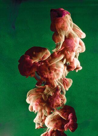 Vloeibare kleur daling van dynamische stroom creëren van interessante en unieke artistieke design. Kleurrijke kleurtinten mengen in het water. Geïsoleerd op een groene achtergrond.