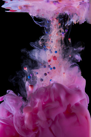 color mixing: Liquid color drop in dynamic flow creating interesting and unique artistic design. Colorful color tones mixing in water. Isolated on black background. Stock Photo