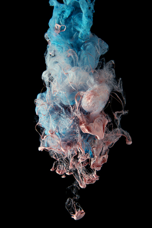 Liquid color drop in dynamic flow creating interesting and unique artistic design. Colorful color tones mixing in water. Isolated on black background. Banque d'images