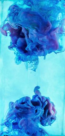 Vloeibare kleur daling van dynamische stroom creëren van interessante en unieke artistieke design. Kleurrijke kleurtinten mengen in het water. Geïsoleerd op cyaan achtergrond. Stockfoto