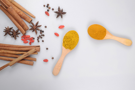 Spices on a wooden spoon isolated on a white background