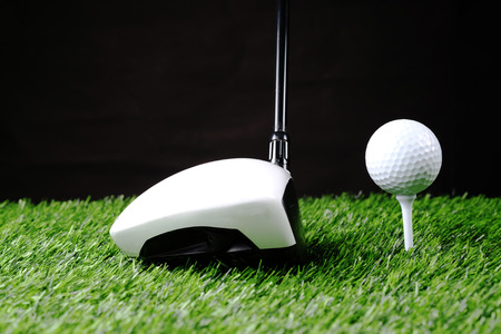 Golf ball on tee in front of driver on a white course Stock Photo