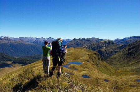 tramping: Two female trampers taking photographs of tarns and mountains on a gorgeous sunny in Green Lake area, Fiordland national park, New Zealand