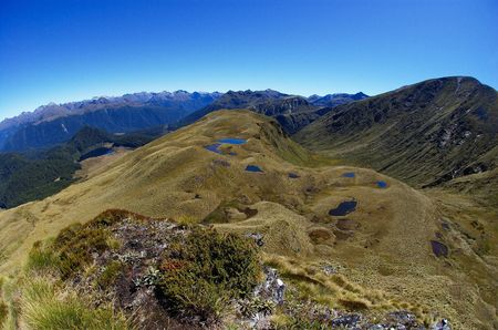 proving: Breathtaking wide-angle view of peaks, tarns and mountain ranges on a gorgeous sunny day in Green Lake area, fish-eye shot proving that the Earth is round shaped, Fiordland national park, New Zealand