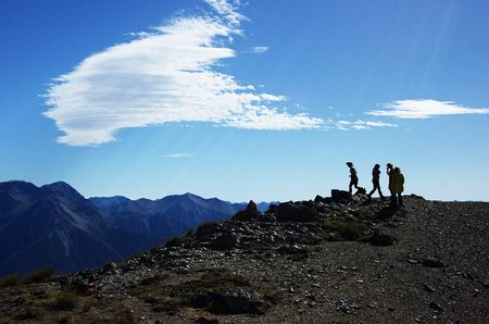tramping: Silhouette of a few trampers on top of Mount Bruce, mountain ranges in the background, Arthurs Pass national park, Craigieburn Forest park, Southern Alps, New Zealand Stock Photo
