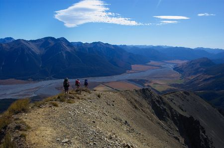 breathtaking: Three trampers in the distance walking along breathtaking mountain ridge, from Mount Bruce down to Waimakariri River valley, Arthurs Pass national park, Craigieburn Forest park, Southern Alps, New Zealand