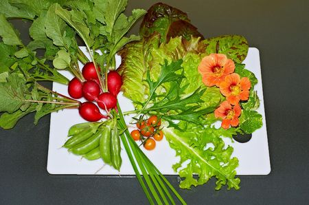Fresh garden salad ingredients on a white chopping board photo