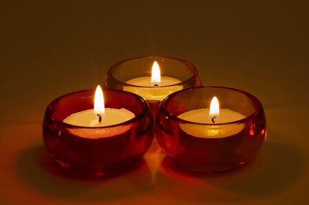 candleholders: Group of three burning tea-lights in coloured glass candle-holders, neutral white background softly illuminated