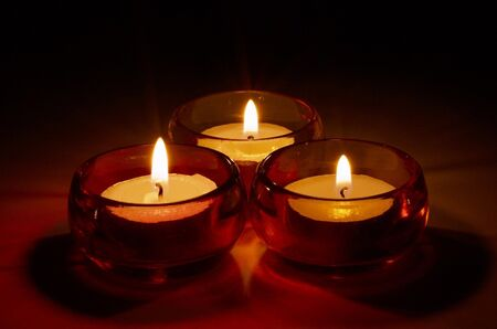 Group of three burning tea-lights in coloured glass candle-holders, neutral background photo