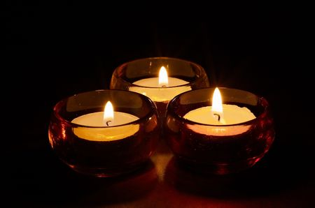 holders: Group of three burning tea-lights in coloured glass candle-holders, dark black background