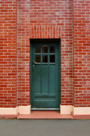 Dark green old wooden door with six glass sections in the upper part, worn-out brass handle, and peeling doorstep, surrounded by a regular red-brick solid wall photo