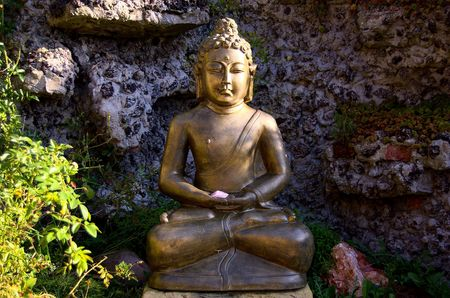 centred: Golder statue of Buddha sitting in the middle of an artificial rock garden with green plants, rose quartz in his hands, morning sunlight coming from the side Stock Photo