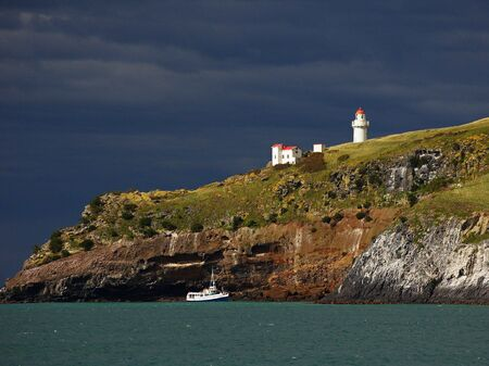 Dramatic view of Tairoa Head with the white lighthouse against dark cloudy sky, small boat passing by the cliffs, Otago harbour, Dunedin, New Zealand photo
