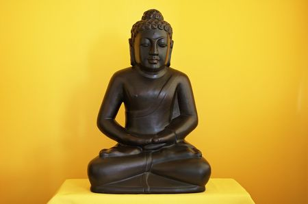 centred: Small statue of Buddha sitting in meditation, plain yellow background, soft light