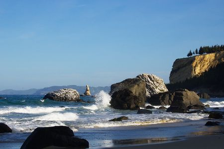 Seacliff-Karitane coast with large basalt rocks on the beach, Otago Peninsula in the background photo
