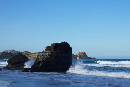 touchstone: Waves crashing against large basalt rocks on the beach around Seacliff-Karitane, New Zealand, sunlit rugged coastline in the background