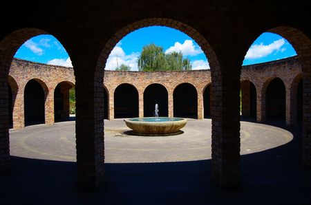 redbrick: Simple fountain in a circular space with red-brick archway around, entrance to Paradise Garden Collection, Hamilton Gardens, New Zealand Stock Photo