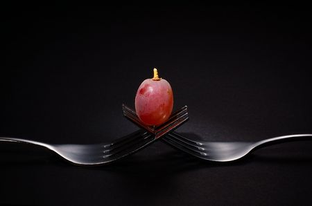 centred: Single red grape sitting centred on top of two intertwined stainless steel forks, black background