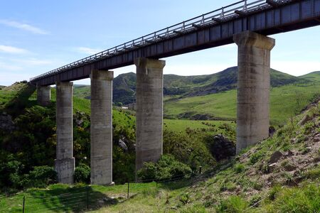 Elegant bridge over Prices Creek with two prominent hills and Taieri River valley in background, Otago Central Rail Trail, New Zealand photo