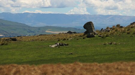 new zeland: Rock formation on a farm, tussock in foreground, Rock and Pillar range in background, Taieri Ridge, Otago, New Zeland Stock Photo