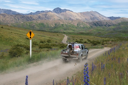 unspecified: Truck driving past an unspecified danger sign on the road through Molesworth Station, The Acheron Road, South Marlborough, New Zealand Stock Photo