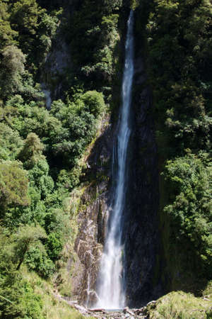 Thunder Creek Falls dropping down to little lagoon by Haast River, West Coast, New Zealand Stock Photo - 12676521