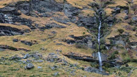 Waterfall and texture of the rocky face with grass hanging on in places, Matukituki Valley, Mount Aspiring National Park, New Zealand photo
