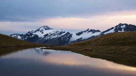 tarn: Mount Aspiring in early morning light and its reflection in the tarn, Mount Aspiring National Park, New Zealand