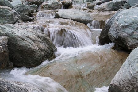 Water of a mountain stream rushing over the boulders, Dart Valley, Mount Aspiring National Park, New Zealand photo