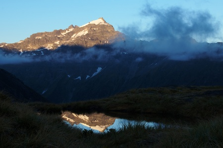 aspiring: Mount Clarke (2285m) in morning sunshine reflecting in a small tarn, Rees Saddle, Mount Aspiring National Park, New Zealand Stock Photo