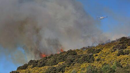 bush fire: Helicopter patrolling bush fire above Outram Glen, Otago, New Zealand