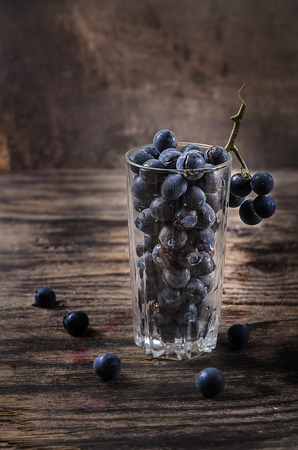 grape juice: On the wooden table is glass with grapes. A glass of grape juice with a straw.