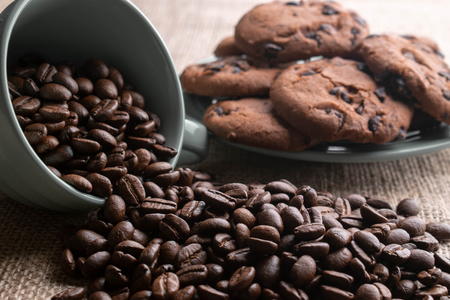 coffee beans crumbled with a cup which is worth on light burlap, in the background plate of cookies