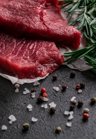 two pieces raw beef steak with fresh rosemary branches lay on parchment paper beside on a dark background scattered large sea salt with red and black pepper peas Stock fotó