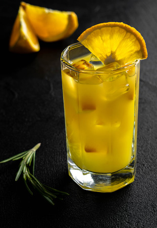 foreground; on a black background glass beaker with orange juice and ice cubes decorates a slice of an orange with green rosemary branch on the background citrus slices
