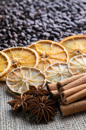 whole coffee beans with dried orange and lime cinnamon sticks and star anise on the background of light burlap