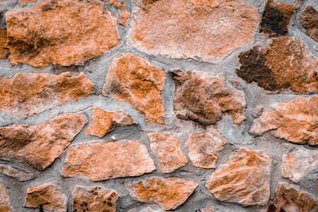The texture of the stone wall. Background of old brown masonry stone with cement.