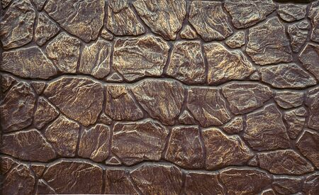 Abstract background imitation of an iron wall of stone.. Texture of brown concrete masonry.