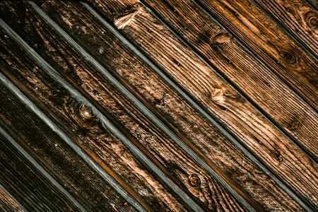 Wooden gate background. A fence made of wood. Texture of a dark log.