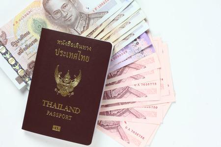 Cash and Thai passport isoled on White photo