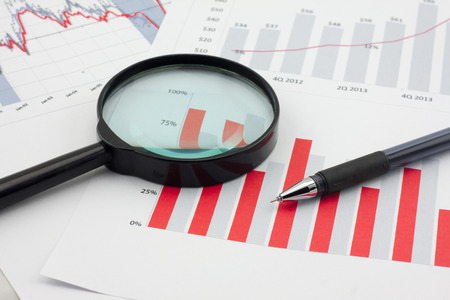 audit: Graphs, magnifier and pen. Analysis charts and graphs of sales.