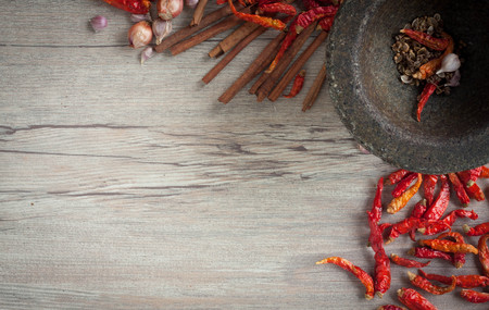 thai chili pepper: Dried Chili and spices in a stone mortar on a wooden table. Can be used as background and texture.