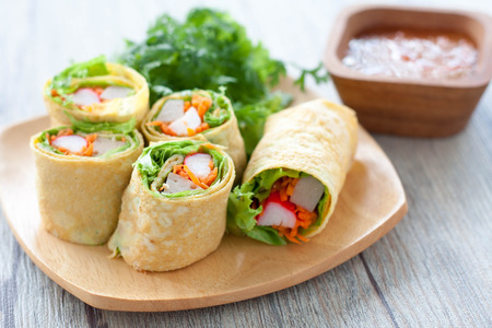 Vegetarian food,Homemade egg rolls and Sweet chili sauce on wood table Imagens